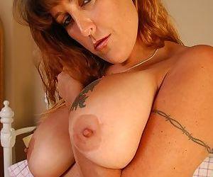 Mature slut in lingerie Katanya presents her huge tattooed breasts proudly