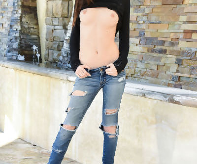 Beautiful teen girl in ripped jeans bares her tits and bald twat on balcony