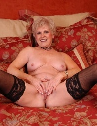 Older blonde lady Jewel letting tits loose from sexy lingerie in stockings
