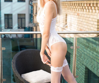 Young blonde girl removes her white lingerie to pose in stockings only