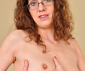 Hot mature in glasses Janice Eros bares small tiny tits and shaved beaver
