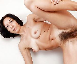 Brunette mature babe uncovering her tiny tits and shaggy pussy
