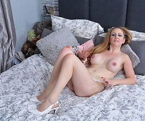 Mature mom with big knockers petting and toying her horny snatch on the bed