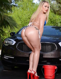 Outdoor posing scene featuring an oiled AJ Applegate in a sexy bikini