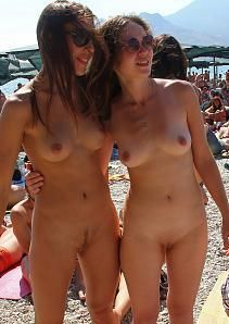 Two pretty friends posing nude on the beach.