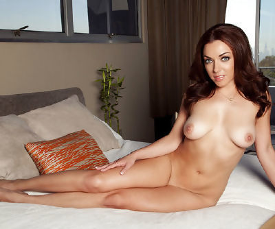Busty babe reveals her perfect shaved pussy and makes lovely leg-split on her bed