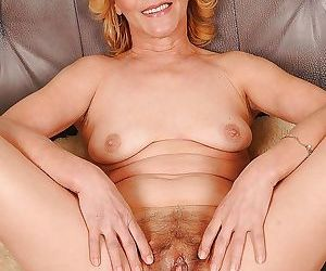 Mature blonde on high heels uncovering her tiny tits and shaggy muff