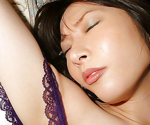 Lascivious asian babe in lingerie teasing her hairy slit on the bed