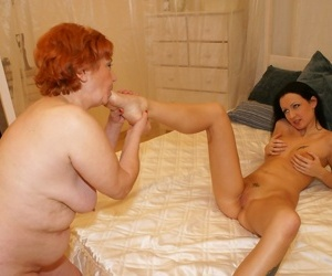 Older redhead and her younger lesbian lover kiss before sucking toes and twats