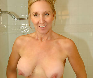 Hot older lady uses a suction dildo to pleasure her pussy in the shower