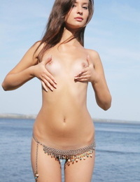 Slim solo girl Isida blows a kiss after modeling naked by the open ocean