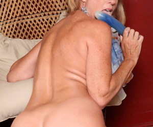 Busty mature woman Jodi West toys her shaved pussy to an orgasm in black pumps