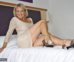 Mature lady works free of short dress and panties in her bedroom