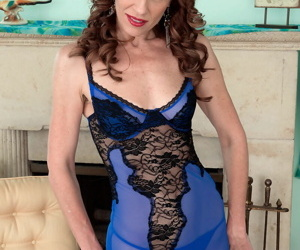 Mature mom Betty Blaze peels off her blue sexy lingerie before the fireplace