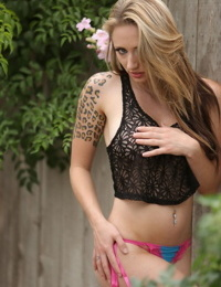 Amateur model Lily Xo poses non nude up against wooden fence