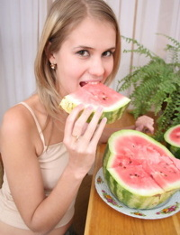 Angelic teen strips off her clothes to pose nude while eating a watermelon