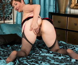 Short haired mature woman Kitty Creamer shows the pink of her twat in bedroom