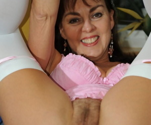 Naughty Georgie lifts her sexy mature legs up and displays trimmed cunt