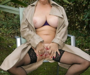 Big titted mature blonde undoes her overcoat before toying her pussy out back