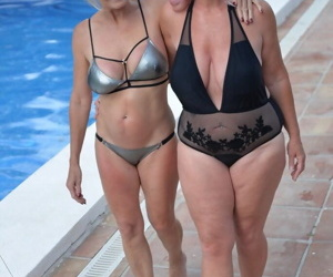 Mature amateurs share a lesbian kiss in their swimwear on poolside patio