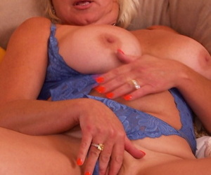 Two busty MILF matures romp on the bed toying & licking nipples