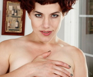 Over-30 redhead Ingrid Mouth peels off her bodysuit to show her pussy
