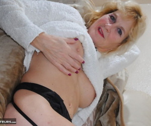 Mature woman frees big tits from sweater in black nylons and high heels
