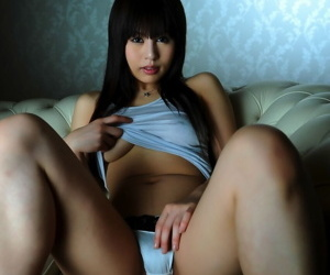 Pretty Japanese girl shows some underboobage on couch in satin panties