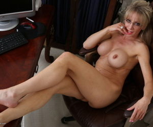 Busty mature blonde in glasses sheds her shirt to bare her big boobs naked