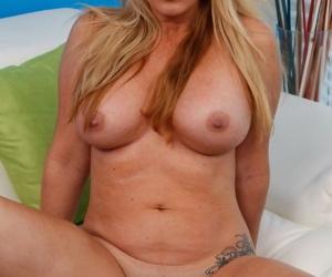 Chubby mature woman Janna Hicks cups her big boobs while disrobing