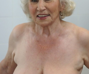 Freaky old blonde granny named Norma showing her tits in the kitchen