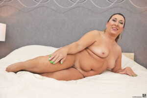 All natural mature granny Jodie spreads her pierced hairy pussy on the bed
