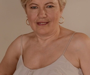 Charming granny Ursula Grande takes her top off and shows natural saggy tits