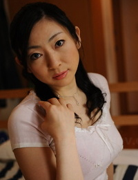 Slim mature Japanese woman Emiko Koike arches over to posture in white dress